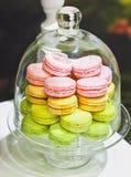Macarons ou macaron français doux et colorés dans un plateau en verre ou en verre de cloche en verre sur une table en bois blanch Images libres de droits