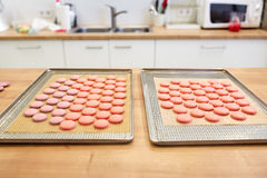 Macarons on oven trays at confectionery. Cooking, confectionery and baking concept - macarons on oven trays at bakery or pastry shop kitchen royalty free stock photos