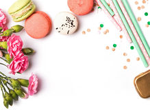 Macarons, paper straws, flowers and confetti on the white backgr Stock Photography