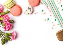 Macarons, pappers- sugrör, blommor och konfettier på den vita backgren Arkivbild