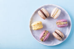 Macarons on plate. Some tasty macarons on a light blue background Royalty Free Stock Photos