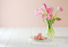 Macarons on plate with tulips Royalty Free Stock Images