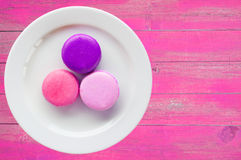 Macarons in plate on vintage pink color wooden Royalty Free Stock Images