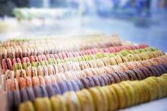 Macarons plus ou moins ronds colorés de bonbons dans une boîte sur l'étalage du Th Image libre de droits