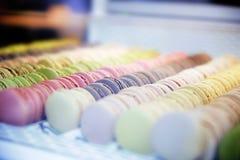Macarons plus ou moins ronds colorés de bonbons dans une boîte sur l'étalage du Th Photos libres de droits
