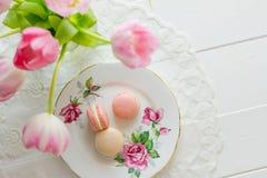 Macarons qui sopra attraverso i fiori Fotografie Stock Libere da Diritti
