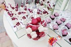 Macarons rojos y blancos en la tabla del abastecimiento de la boda con diferente Foto de archivo