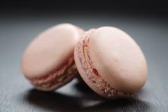 Macarons rosa-chiaro sul fondo dell'ardesia Immagini Stock