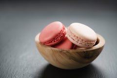 Macarons rosa in ciotola sul fondo dell'ardesia con lo spazio della copia Fotografie Stock Libere da Diritti