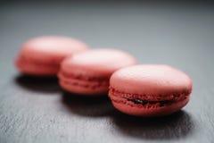 Macarons rosa luminosi sul fondo dell'ardesia Fotografie Stock