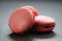 Macarons rosa luminosi sul fondo dell'ardesia Fotografie Stock Libere da Diritti