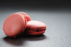 Macarons rosa luminosi sul fondo dell'ardesia con lo spazio della copia Fotografia Stock