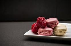 Macarons roses avec des framboises Fond foncé Photos libres de droits