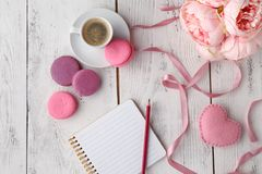 Macarons roses avec la tasse de café sur la table en bois Configuration plate photos stock