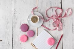 Macarons roses avec la tasse de café sur la table en bois Configuration plate photographie stock