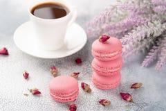 Macarons roses avec les bourgeon floraux et la tasse de café secs pastel photographie stock libre de droits