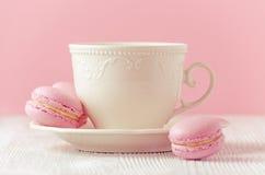 Macarons roses faits maison et une tasse de café sur le fond rose modifié la tonalité Images stock
