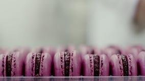 Macarons roses prêts avec la confiture dans l'emballage, vue en gros plan