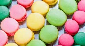 Macarons savoureux colorés sur la table en bois avec des fleurs, une délicatesse douce française, texture de macaron Photo libre de droits