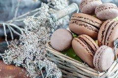 Macarons sensibles de meringue d'amande dans un panier en osier sur la table Plan rapproché image stock