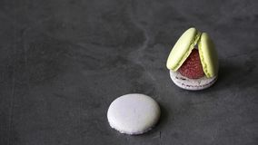 Macarons shells with raspberries on dark background royalty free stock image