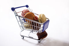 Macarons in a shopping cart. Blue shopping cart full of macarons, out of the shop Royalty Free Stock Photography