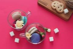 Macarons in tazza di vetro con i fiori e lo zucchero sui precedenti rosa Scrittorio di legno con i biscotti Vista superiore Fotografia Stock