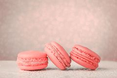 Living Coral color of the Year 2019 Macarons on glitter bokeh ba. Macarons toned in Living Coral color of the Year 2019. Color palette, glitter bokeh background stock photo