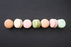 Macarons, top view flat lay, sweet macaroon on black slate Stock Images