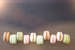 Macarons, top view flat lay, sweet macaroon on black slate Royalty Free Stock Photo