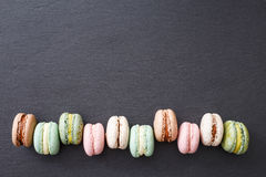 Macarons, top view flat lay, sweet macaroon on black slate Royalty Free Stock Image