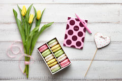 Macarons, tulips and notebook on wooden table Royalty Free Stock Photography
