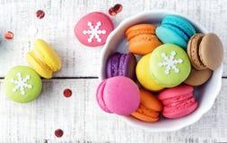 Macarons variopinti con la decorazione di natale sulla tavola di legno bianca Immagini Stock