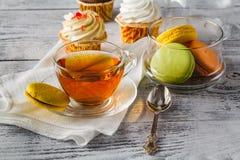 Macarons variopinti francesi con la tazza di caffè nero Piacere dolce Immagine Stock