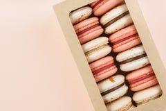 Macarons variopinti in un contenitore di regalo su fondo rosa Vista superiore immagini stock