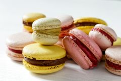 Macarons of various colors and sizes. White background.  stock photos