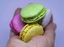 Macarons verdes, amarelos, cor-de-rosa e brancos em uma mão do ` s Fotos de Stock
