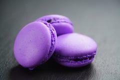 Macarons violetas brillantes en fondo de la pizarra Foto de archivo libre de regalías