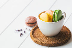 Macarons on white wooden background. Coloured macarons in cup on white wooden background Royalty Free Stock Photography