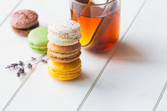 Macarons on white wooden background. Macarons stack with tea on white wooden background royalty free stock images