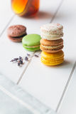 Macarons on white wooden background. Macarons stack with tea on white wooden background royalty free stock photo