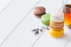Macarons on white wooden background. Macarons stack with tea on white wooden background royalty free stock image