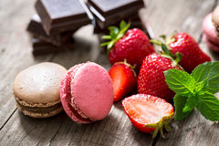 Macarons on a wooden plate with fresh strawberry fruits Stock Images