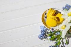 Macarons y flores en un fondo blanco Postre francés colorido con las flores frescas Visión superior Postre francés encendido fotos de archivo libres de regalías