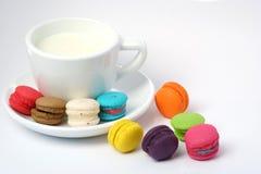 Macarons y taza coloridos de la leche Foto de archivo