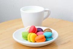 Macarons y taza coloridos de la leche imagenes de archivo