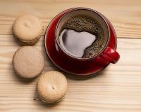 Macarons y taza de café roja en un fondo de madera ligero Fotografía de archivo