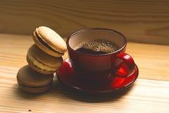 Macarons y taza de café roja en un fondo de madera ligero tonelada imagen de archivo libre de regalías