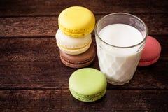 Macarons y vidrio coloridos de leche en fondo de madera oscuro imagenes de archivo
