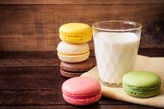 Macarons y vidrio coloridos de leche en fondo de madera oscuro foto de archivo